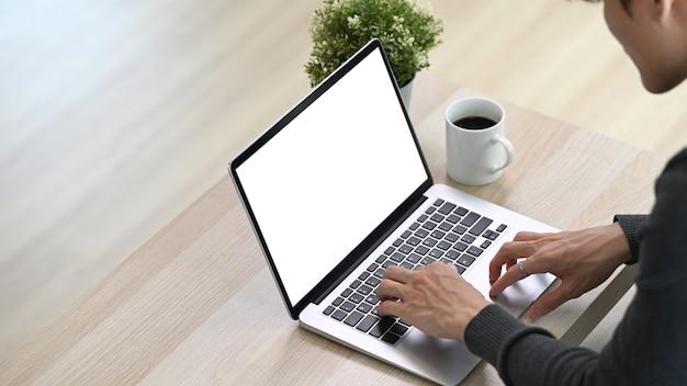 Kurzer schuss des freiberuflers des jungen mannes, der auf der couch im wohnzimmer sitzt und mit laptop arbeitet.
