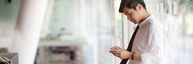 Kurzer schuss des männlichen unternehmers machen kurze pause und entspannen mit smartphone