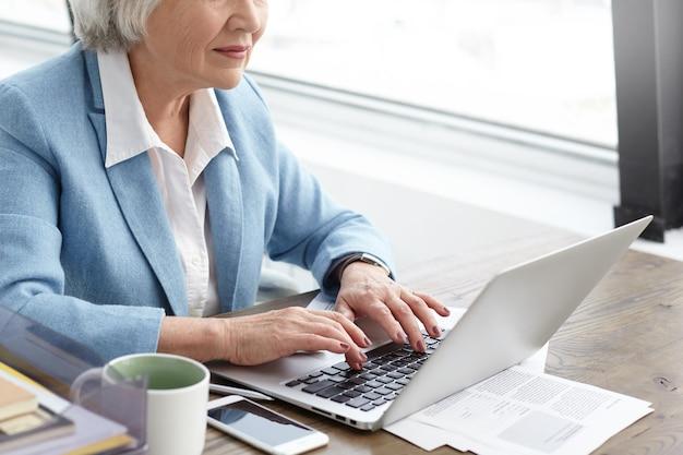 Kurzer schuss einer älteren geschäftsfrau mit grauem haar und faltigen händen, die auf laptop schreiben, während sie in ihrem büro arbeiten. stilvolle reife kaukasische frau, die blauen anzug mit geräten für die arbeit trägt