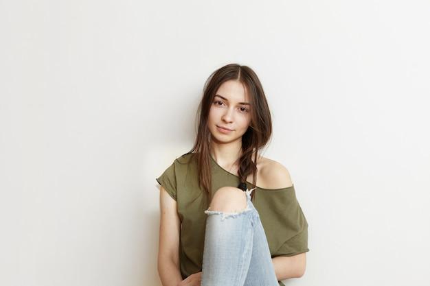 Kurzer schuss einer attraktiven jungen frau, die ihre lange dunkelheit in einem unordentlichen zopf trägt, der sich zu hause entspannt, auf dem boden sitzt, sich auf eine weiße leere wand zurücklehnt, gekleidet in ein stilvolles übergroßes oberteil und zerlumpte jeans