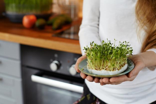 Kurzer schuss einer frau, die in ihren händen eine untertasse mit einem selbst angebauten bio-sprossen-mikrogrün gegen gemütliches kücheninterieur hält. gesundes rohkostkonzept. kopieren sie platz für text. selektiver fokus