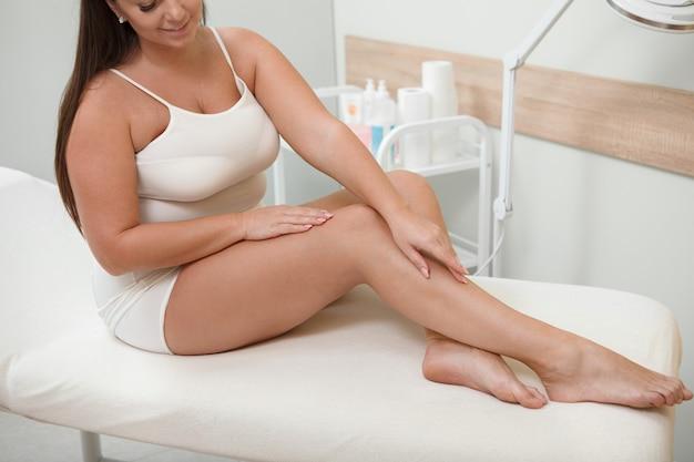 Kurzer schuss einer glücklichen frau mit kurvigem körper, der ihre haut nach kosmetologischer behandlung berührt