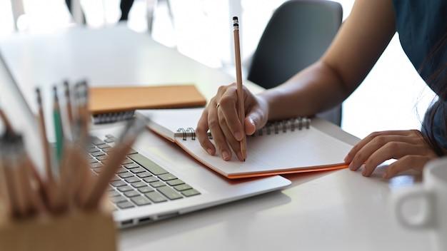 Kurzer schuss einer jungen geschäftsfrau, die ihre strategie auf ihr notizbuch schreibt