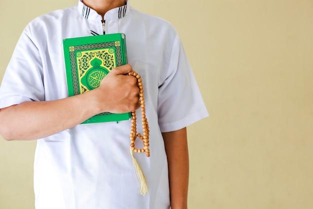 Kurzer schuss eines muslimischen mannes, der das heilige buch alquran und gebetsperlen in seiner hand hält
