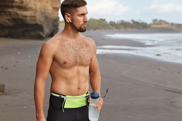 Kurzer schuss eines sportlichen mannes hat muskulösen körper macht pause und trinkt frisches wasser