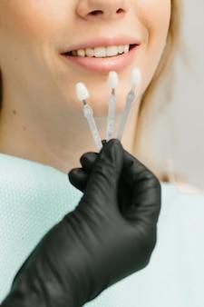 Kurzer schuss von arzt und patient, die zahnimplantate in der modernen zahnklinik wählen