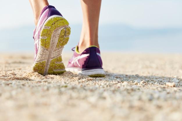 Kurzer schuss von frauenbeinen in lila trainingsschuhen steht am sandstrand an der küste
