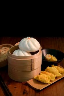 Kurzer schuss von hausgemachten chinesischen knödeln und brötchen, die auf einem traditionellen dampfgarer serviert werden