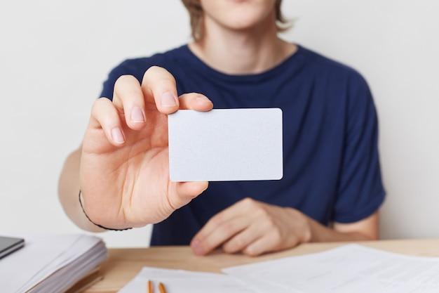Kurzer schuss von jungen männlichen händen hält leere karte mit kopienraum für ihren text oder werbeinhalt