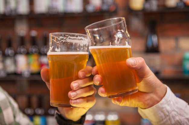Kurzer schuss von männlichen freunden, die an biergläsern klirren