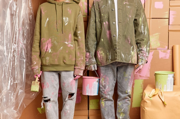Kurzer schuss von schmutziger frau und mannarbeit als team hält farbeimerpinsel, die haus nach umzug malen, tragen freizeitkleidung imrpove wohnung. hausrenovierung. teamarbeit und renovierungskonzept
