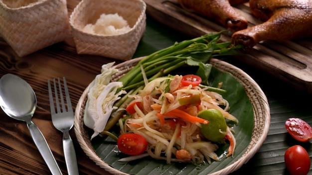 Kurzer schuss von somtum, traditionelles thailändisches essen mit klebreis, gegrilltem hühnchen und besteck