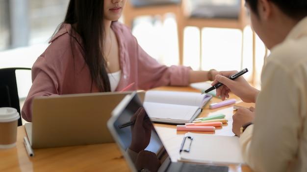 Kurzer schuss von zwei universitätsstudenten, die im modernen café sitzen