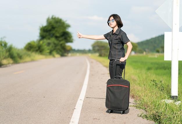 Kurzes haar der jungen asiatischen frau und das tragen der sonnenbrille mit dem trampen des gepäcks entlang einer straße und daumen hoch in der landstraße thailand