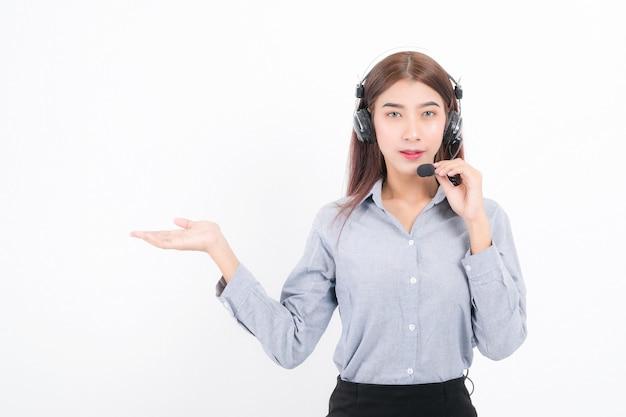 Kurzes haar des kundenbetreuungs-telefonbetreibers, tragend ein graues hemd mit headset, das eine seite steht und den kopfhörer lokalisiert auf weißem hintergrund hält.