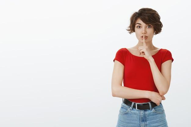 Kurzes haarmädchen, das im roten t-shirt aufwirft