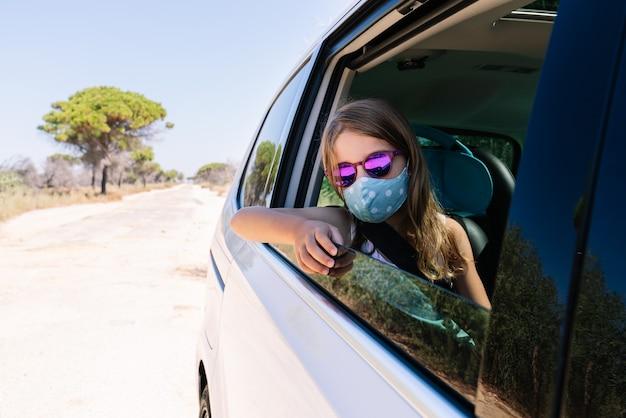 Kurzes mädchen mit blonden haaren mit gesichtsmaske und sonnenbrille, die aus dem autofenster späht und in den urlaub auf einer kiefernstraße mitten in der covid19-coronavirus-pandemie fährt