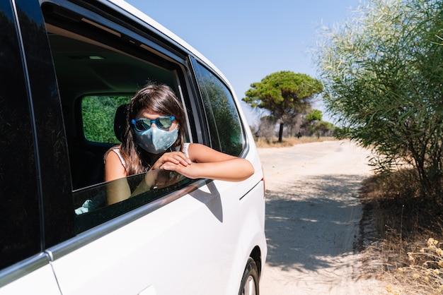 Kurzes mädchen mit braunen haaren mit gesichtsmaske und sonnenbrille, die aus dem autofenster späht und in den urlaub auf einer kiefernstraße mitten in der covid19-coronavirus-pandemie fährt