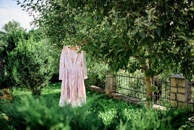 Kurzes rosa kleid hängt auf dem pflock in einem grünen garten