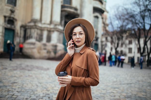 Kurzhaarige dame, die über phote und textnachrichten auf ihrem telefon spricht