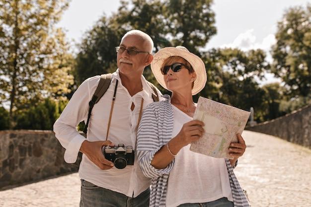 Kurzhaarige dame im hut, kühle sonnenbrille und gestreifte blaue kleidung, die karte hält und mit mann in gläsern und weißem hemd mit kamera im park aufwirft.
