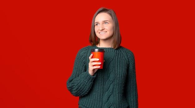 Kurzhaarige frau denkt und schaut weg, während sie eine tasse kaffee zum mitnehmen hält.