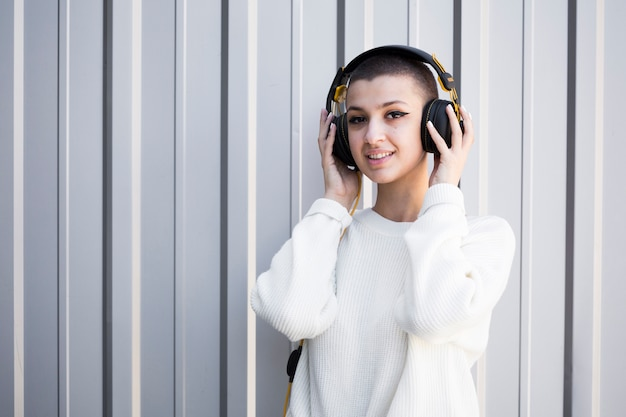 Kurzhaarige frau, die musik mit kopfhörern hört