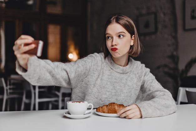 Kurzhaarige frau im kaschmir-sweatshirt bestellte croissant und cappuccino im cafe und macht selfie.