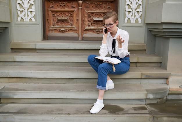 Kurzhaarige frau mit brille, die mit einem buch lifestyle durch die stadt spaziert. foto in hoher qualität