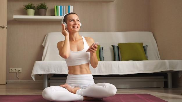 Kurzhaarige frau mit kopfhörern sitzt im wohnzimmer auf einer fitnessmatte in selbstisolation
