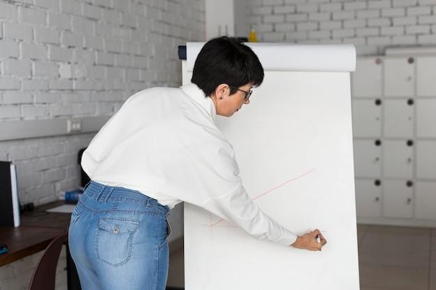 Kurzhaarige geschäftsfrau, die eine karte zeichnet