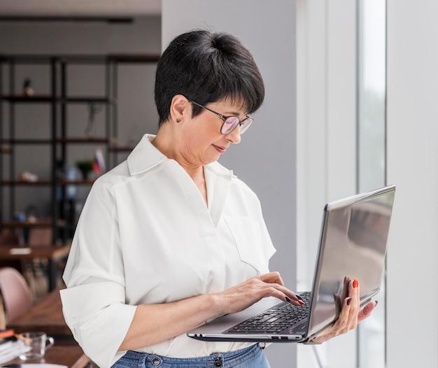 Kurzhaarige geschäftsfrau, die ihren laptop im stehen benutzt