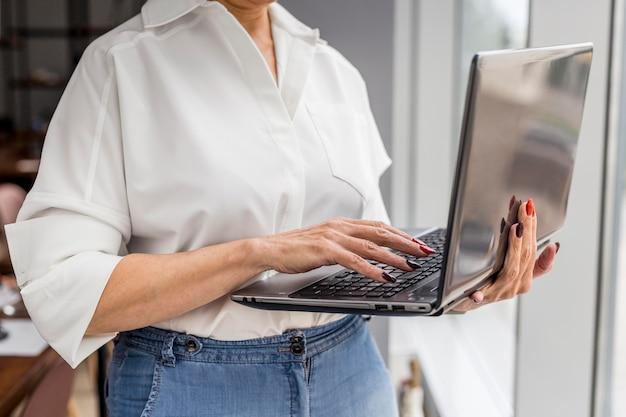 Kurzhaarige geschäftsfrau, die laptop hält