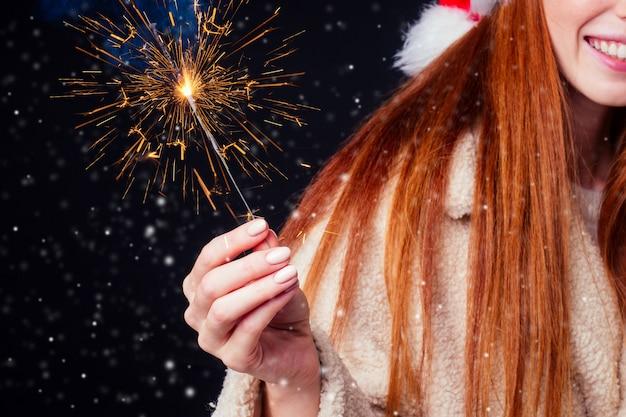 Kurzhaarige ingwerfrau mit abgeschnittenem schuss in warmem schafswollmantel und weihnachtsmannhut mit bengal-wunderkerze und weißer ratte