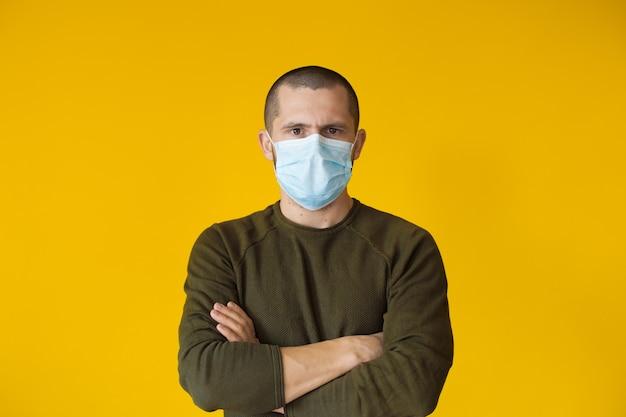 Kurzhaariger kaukasischer mann, der eine weiße maske trägt, posiert auf einer gelben wand mit gekreuzten händen