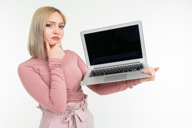 Kurzhaariges mädchen mit weißen haaren zeigt einen laptop-bildschirm mit einem leeren rohling auf einem weißen studiohintergrund