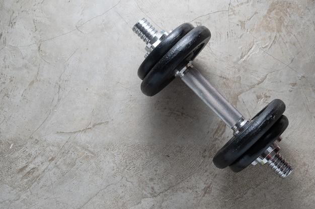 Kurzhanteln für muskelaufbauübungen auf zementboden mit copyspace platziert. körpertraining im fitness-trainingskonzept. neue normale beliebte lebensstile für starkes und gesundes bodybuilding zu hause