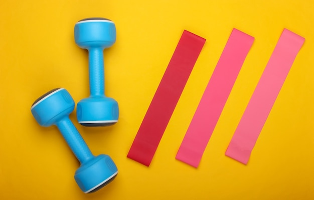 Kurzhanteln mit fitnessgummibändern auf gelbem grund. draufsicht, flach liegen