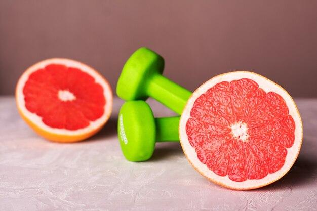 Kurzhanteln und grapefruit auf weißem hintergrund. fitness und gesunde ernährung lifestyle-konzept.