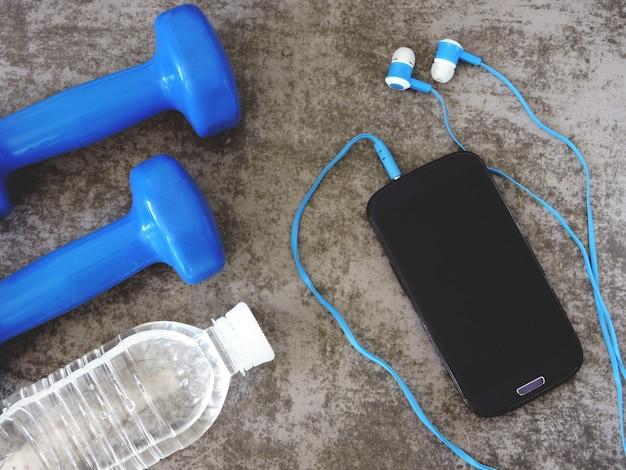 Kurzhanteln, wasser, telefon mit kopfhörer. das konzept von fitness und aktivem lebensstil.