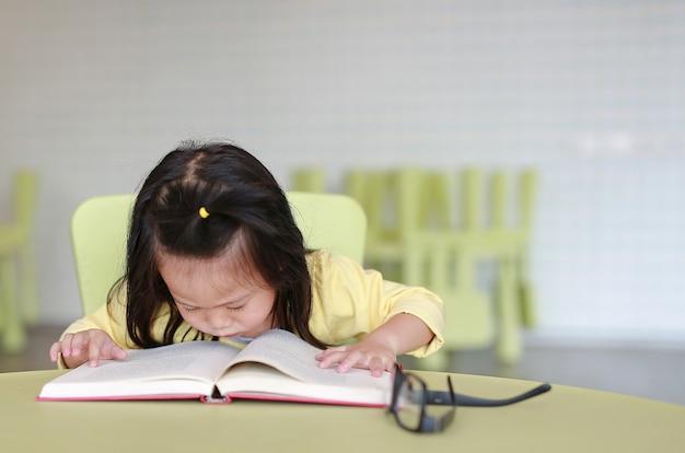 Kurzsichtiges kleines kindermädchen, das ein buch im kinderraum liest.