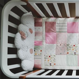 Kuscheliges babybett mit rosa patchworkdecke
