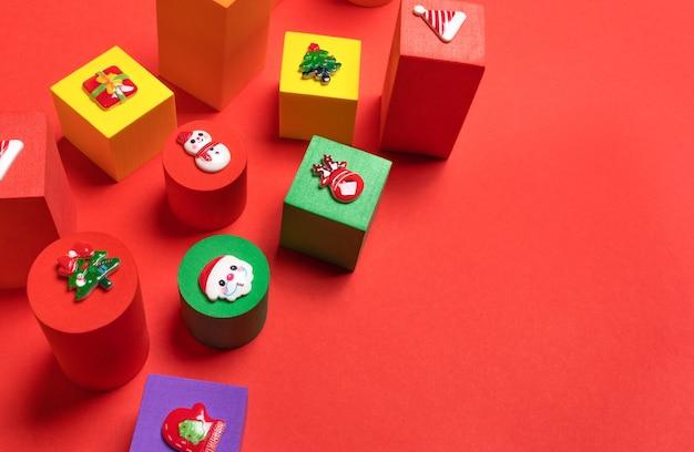 Kuscheltiere bunte kinderwürfel in verschiedenen größen mit weihnachtssymbolen oben auf rotem hintergrund hautnah. weihnachtsdekorationen. ansicht von oben. kopieren sie platz für text.