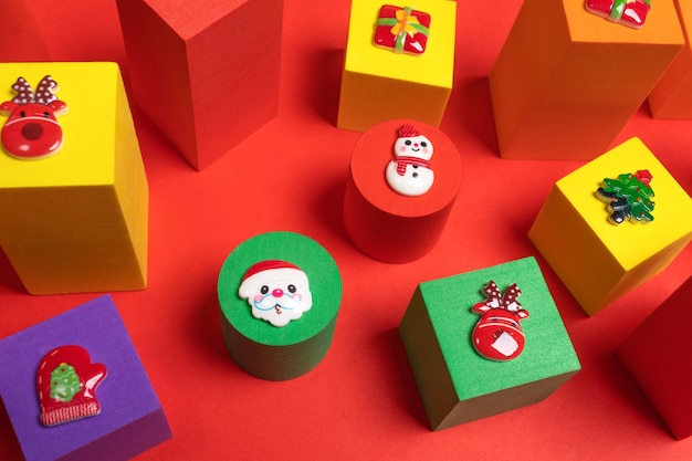 Kuscheltiere bunte kinderwürfel in verschiedenen größen mit weihnachtssymbolen oben auf rotem hintergrund hautnah. weihnachtsdekorationen. von oben betrachten.