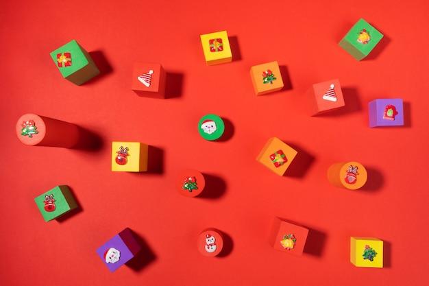 Kuscheltiere bunte kinderwürfel mit weihnachtssymbolen oben auf rotem hintergrund. anordnung der weihnachtsdekoration. ansicht von oben.