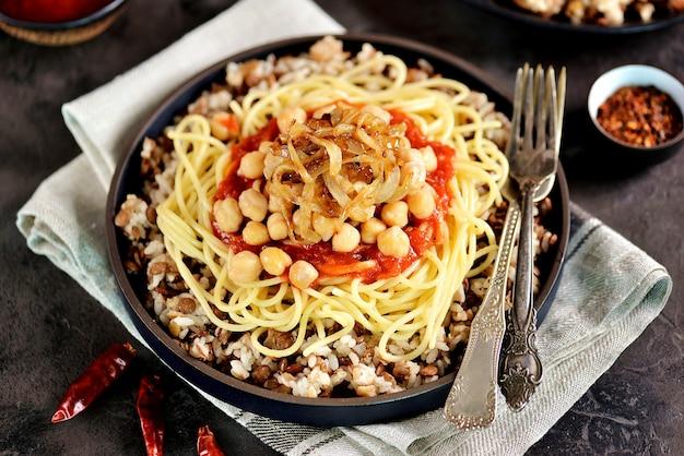 Kushari oder koushari - ägyptisches gericht aus linsen, reis, nudeln, kichererbsen mit tomatensauce und knusprigen zwiebeln. arabische küche