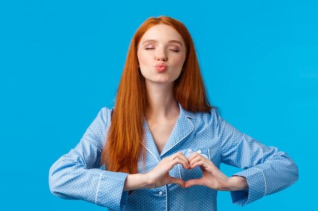 Kuss für eine gute nacht. charmante hübsche rothaarige frau im pyjama falten lippen und schließen augen geben mwah, zeigt herzgeste über der brust, drücken zuneigung oder zarte gefühle aus, blaue wand