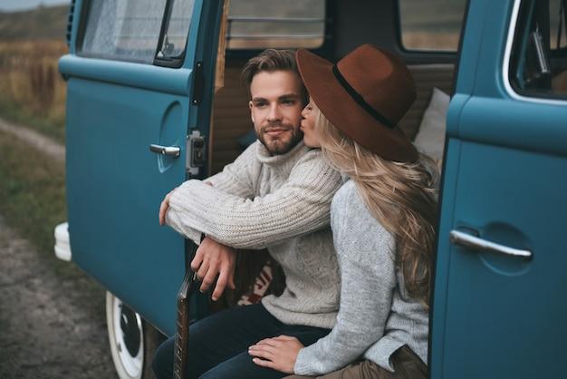 Kuss voller liebe. schöne junge frau, die ihren freund küsst, während sie im blauen retro-art-minivan sitzt