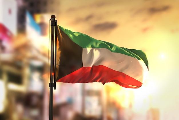 Kuwait-flagge gegen stadt verschwommen hintergrund bei sonnenaufgang hintergrundbeleuchtung