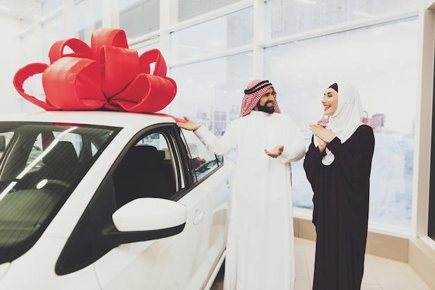 Kuwaitischer mann kauft auto für frauenaraber im ausstellungsraum